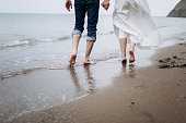 Two pairs of legs of lovers walk on the sand on the seashore. Lovers and newlyweds. Walk in nature.