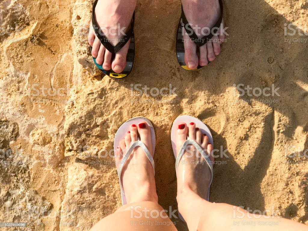 1371c570c334c Two Pairs Of Male And Female Legs With A Manicure In Slippers A Foot ...