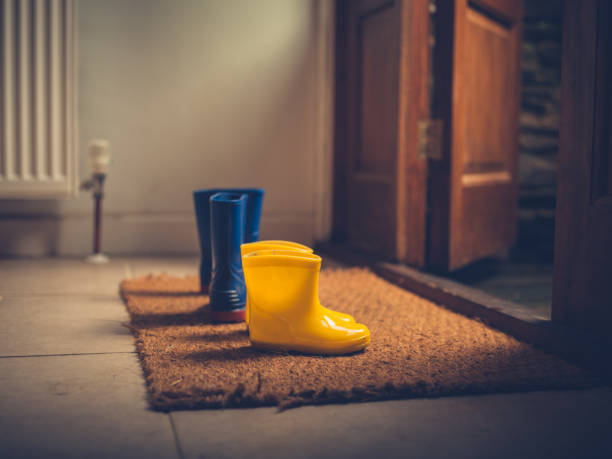 Two pairs of rubber boots by door stock photo