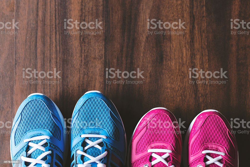 Two pairs of running shoes in blue and pink on wooden floor