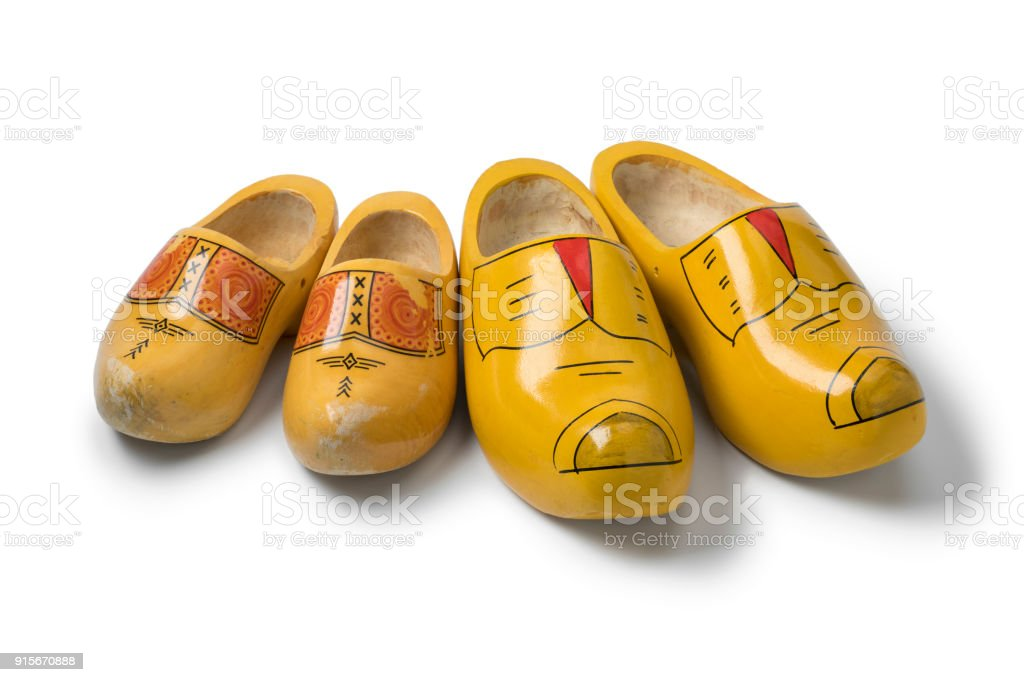 Two pairs of traditional yellow Dutch wooden shoes stock photo