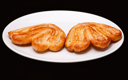 Two palmier biscuits with sugar on the white plate close-up