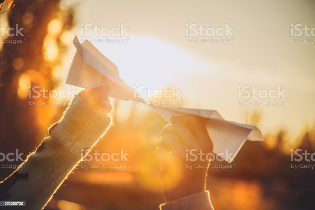 Two paper airplanes in hands looking at each other at sunset stock photo