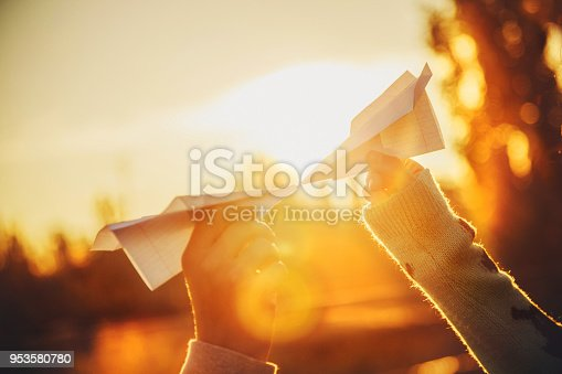 istock Two paper airplanes in hands looking at each other at sunset. Young people holding paper aeroplanes, love, relations concept 953580780