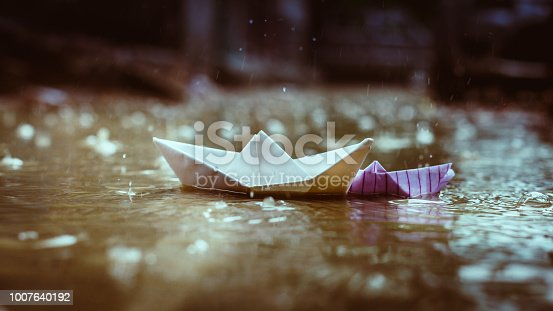 One small and one big paper Boats floating in water puddle during monsoon rains