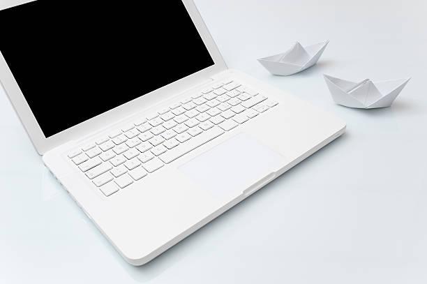 zwei papier-boote in der nähe von laptop - origami mobil stock-fotos und bilder