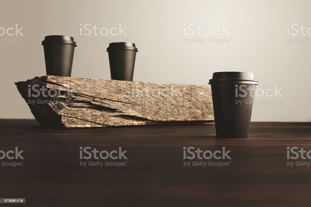 Two paper cups unfocused one in focus isolated wooden table stock photo
