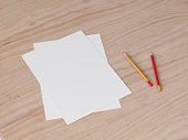Two Paper sheets with pencils on wooden table