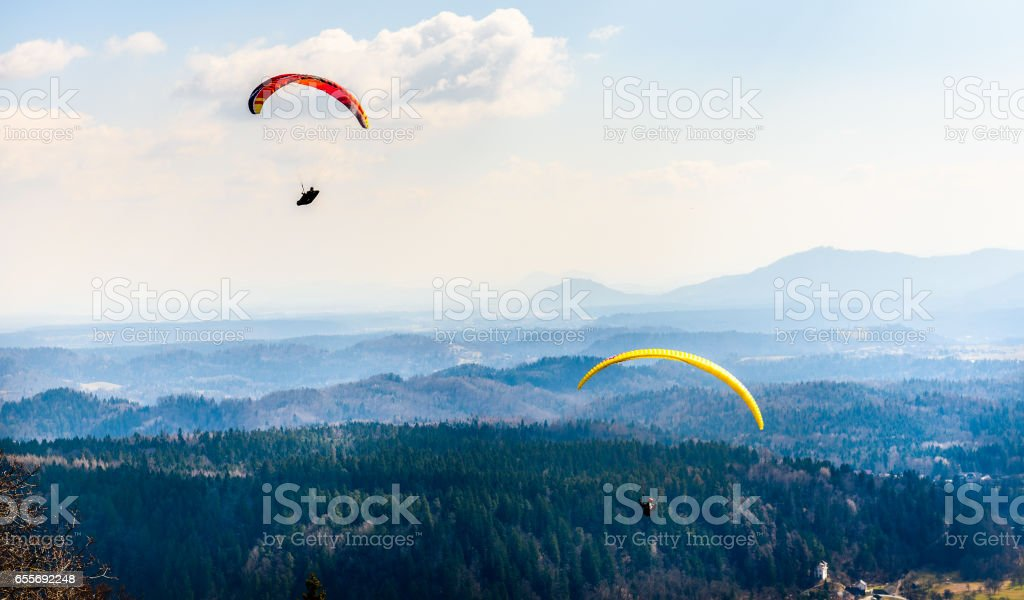 Dos parapentes están volando en el valle. - foto de stock
