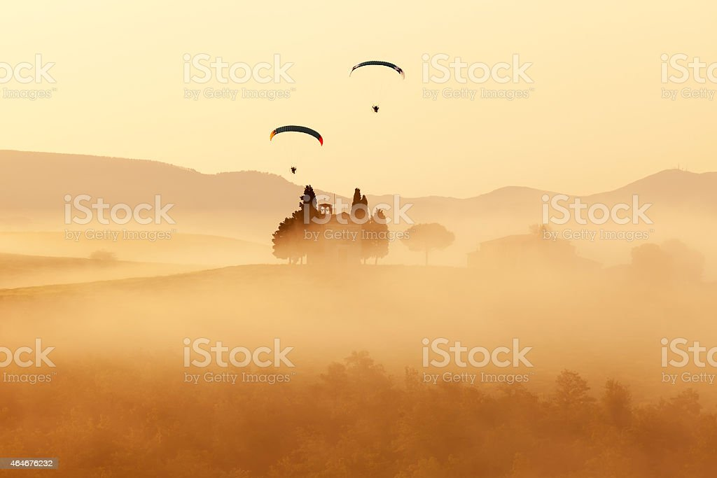 Two Paragliders Over Old Chapel, Tuscany, Italy stock photo