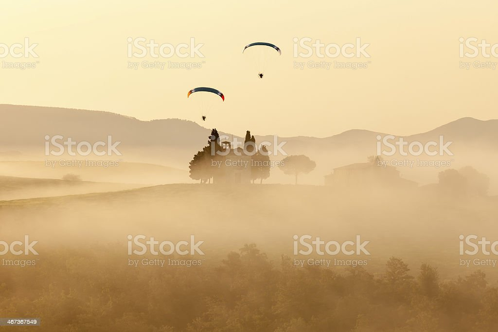 Two Paragliders Over Vitaleta Chapel at Dawn, Tuscany, Italy stock photo