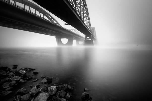 Two parallel bridges over foggy river. Long exposure shot. Two parallel bridges over foggy river. Long exposure shot. Dniepr. Kiev. Ukraine. railway bridge stock pictures, royalty-free photos & images