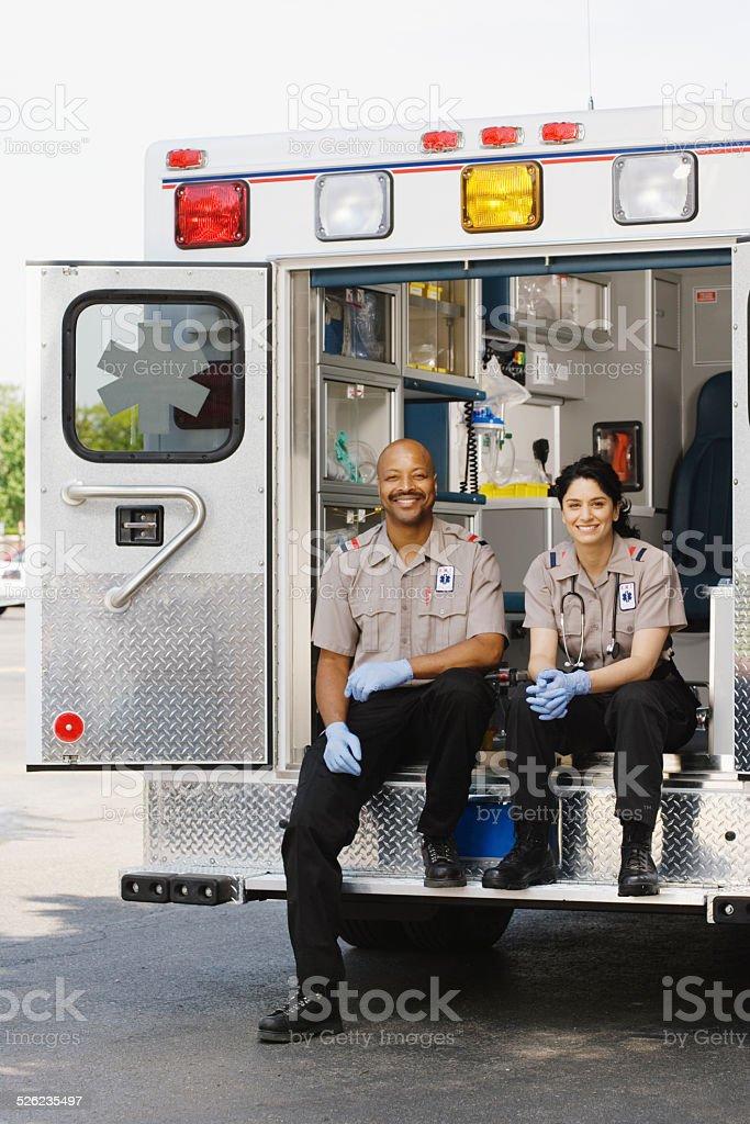 Deux auxiliaires médicaux assis dans une ambulance, portrait - Photo