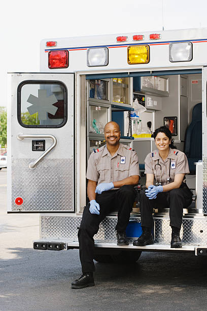 Two paramedics sitting in ambulance, portrait Two paramedics sitting in ambulance, portrait ambulance staff stock pictures, royalty-free photos & images