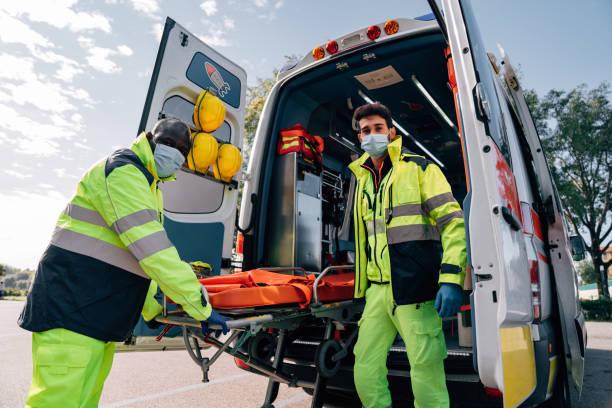 Two paramedics with a stretcher near an ambulance stock photo