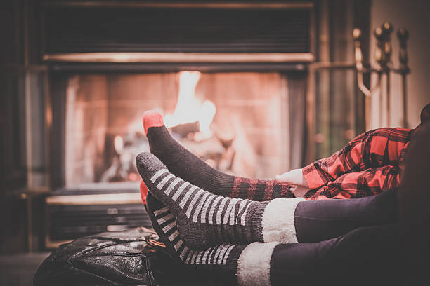 Two parents and baby feet Warming by Fireplace stock photo