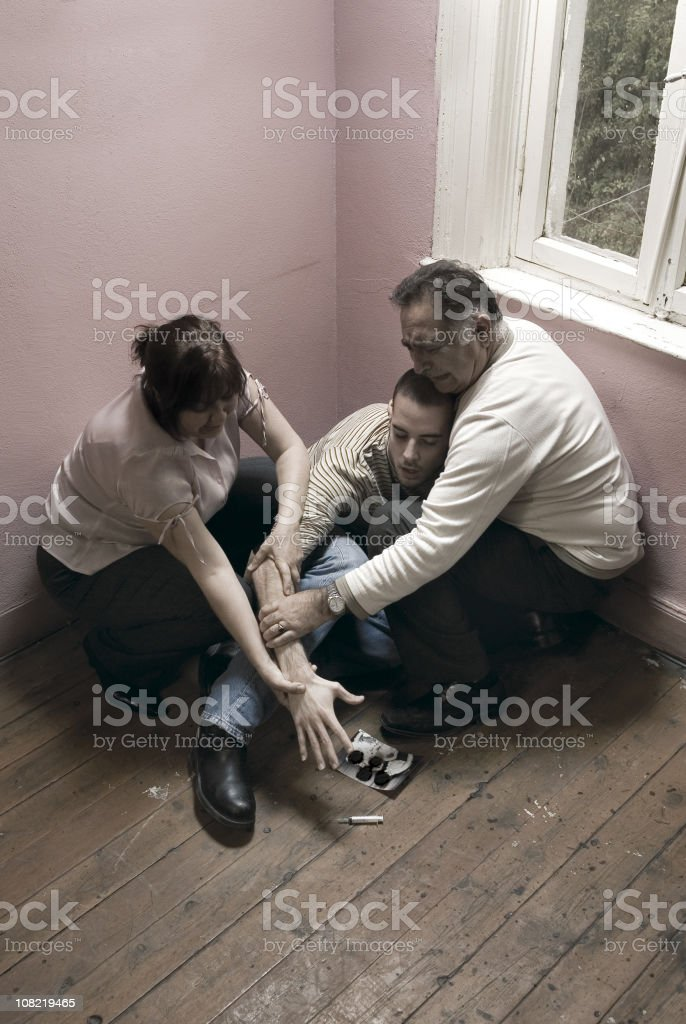 Two Parents Hold Young Man's Arm From Reaching Syringe stock photo