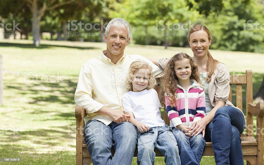 Two parents holding their children while sitting on park bench royalty-free stock photo