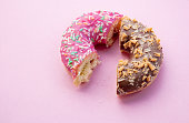 istock Two parts of donuts, pink and chocolate 984264618
