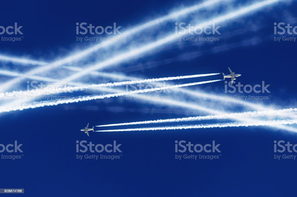 Two passenger airplanes met at altitude and were crossed by courses aviation airport contrail clouds. stock photo