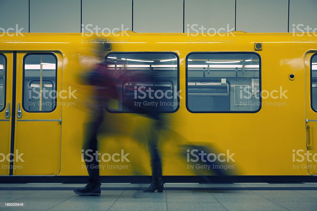 Two Passengers Walking in Front of Subway Train, Pulling Luggage royalty-free stock photo
