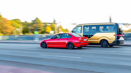 Two passing cars in the city center of Hamburg with motion blurred background