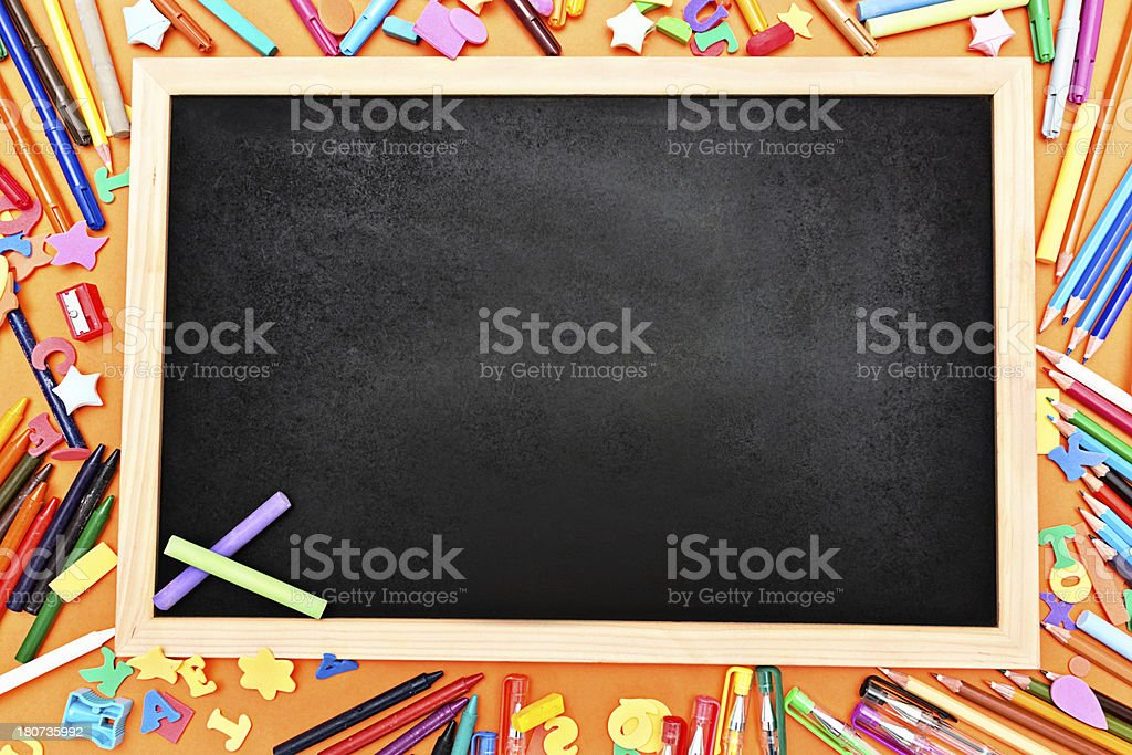 Two pastel chalks on blank blackboard surrounded by stationery royalty-free stock photo
