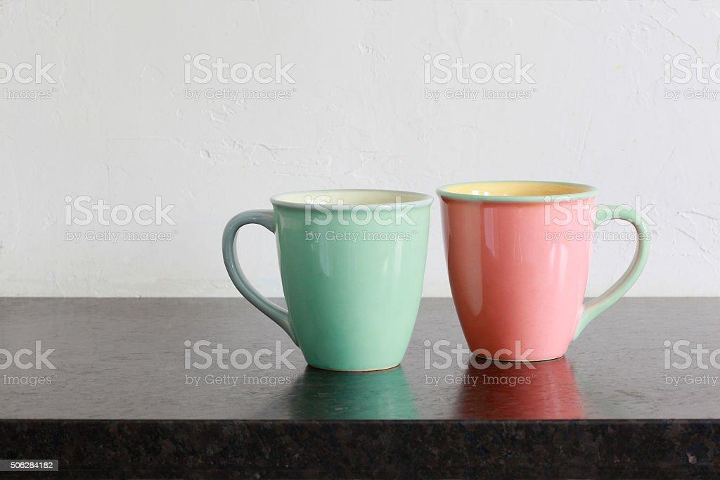 Two pastel mugs on black granite kitchen countertop