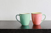 Two pastel mugs on black granite kitchen countertop