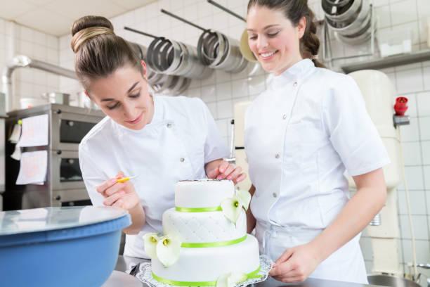 zwei kuchen bäcker großen kuchen dekorieren - hausgemachte hochzeitstorten stock-fotos und bilder