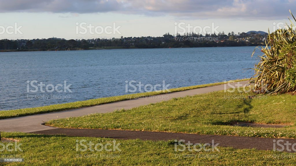 Two Paths meeting next to a blue lake stock photo