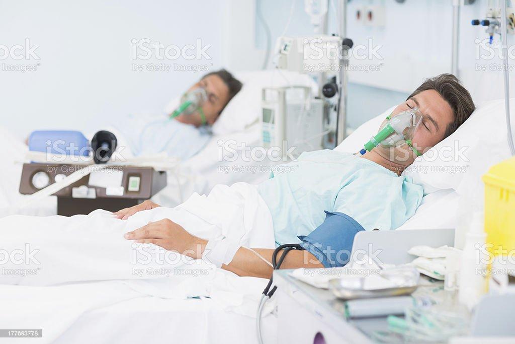 two patients in hospital beds wearing oxygen masks royaltyfree stock photo
