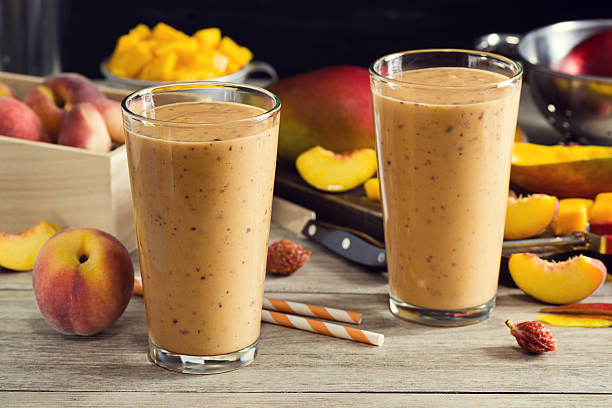Two Peach Mango Smoothies in Glasses with Ingredients stock photo
