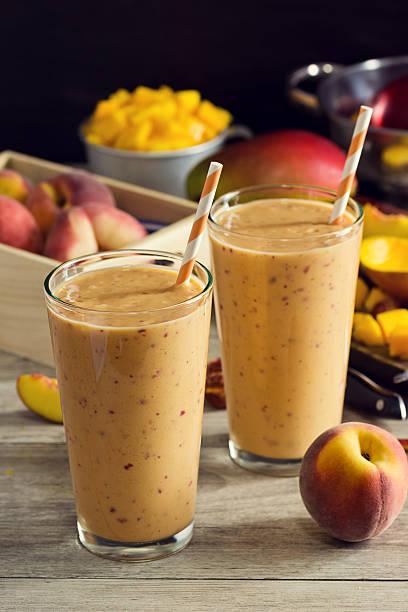 zwei peach mango-smoothie in glas mit zutaten - pfirsich milchshake stock-fotos und bilder