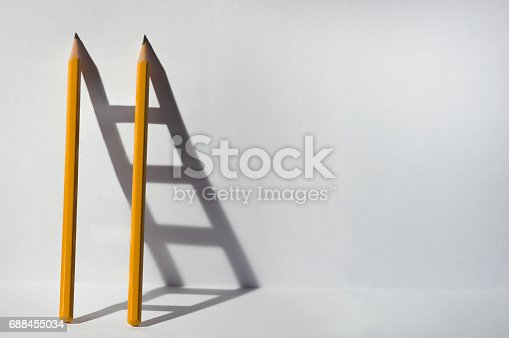 istock Two pencils and a shadow in the form of staircase. Success, teamwork and solving problems business concept. 688455034