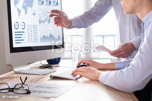 istock Two people analyzing stock market investment strategy on computer 811465460