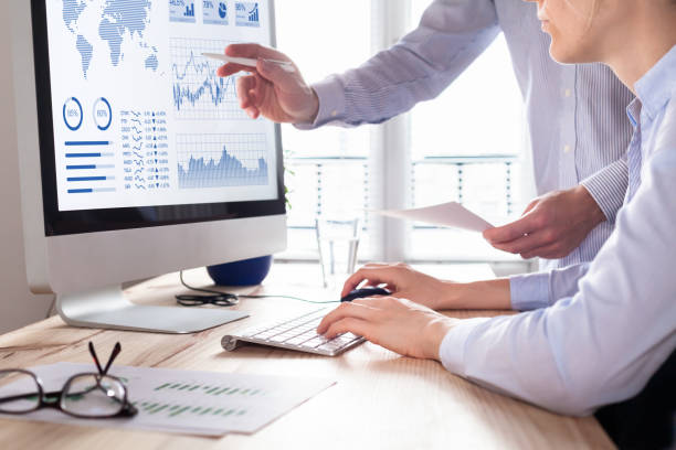 Two people analyzing stock market investment strategy on computer stock photo