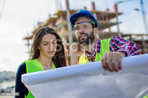 617878058 istock photo Two people at construction site looking at blueprints 618947806
