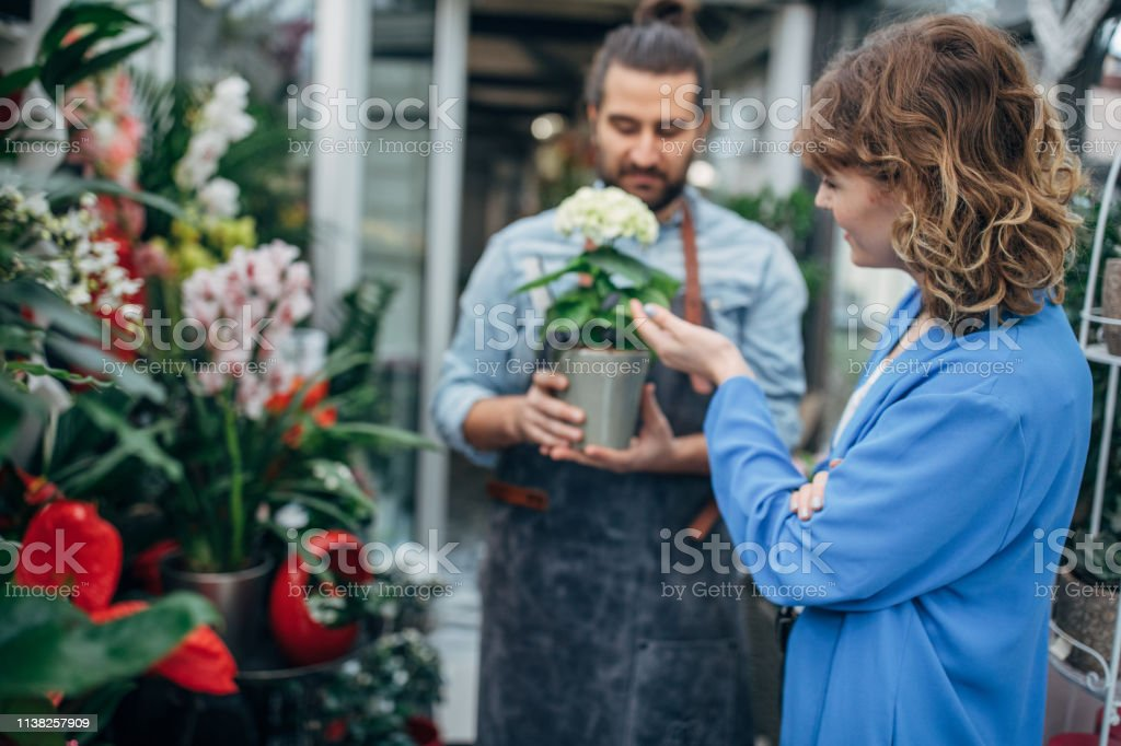 Florist and his customer at the flower shop.