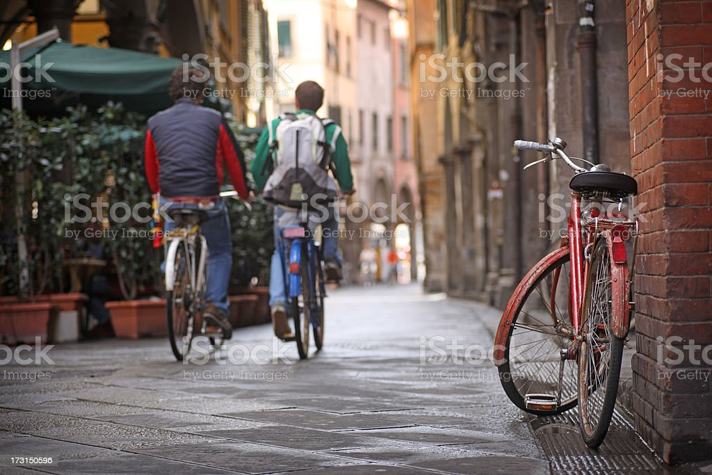 Two people bicycling in Pisa, Italy royalty-free stock photo
