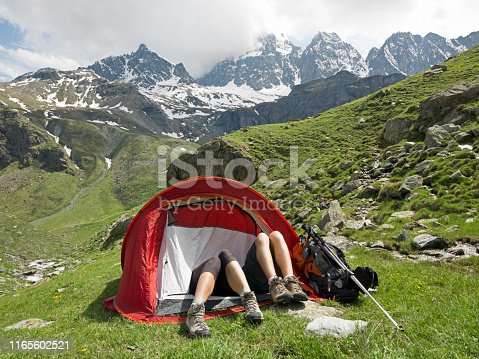 Just their legs are sticking out of the tent and snowcapped peaks behind