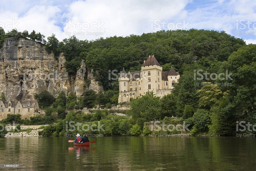 Two people canoeing in a lake near a castle stock photo