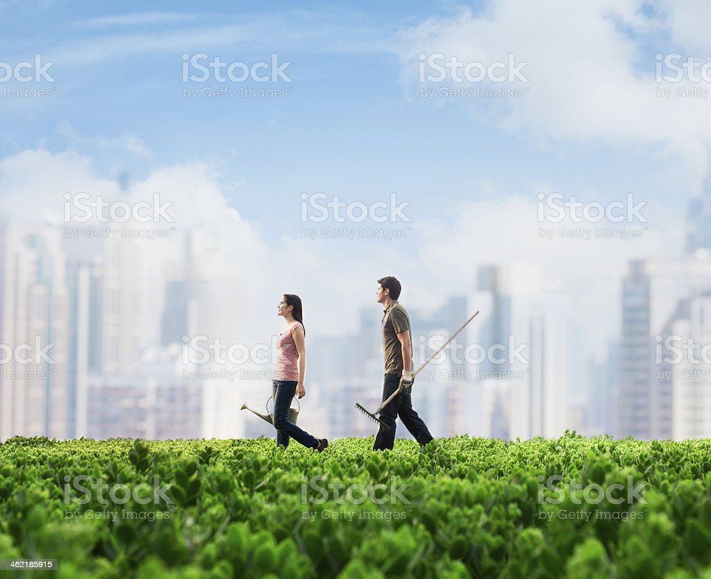 Two people carrying gardening equipment walking across green field stock photo
