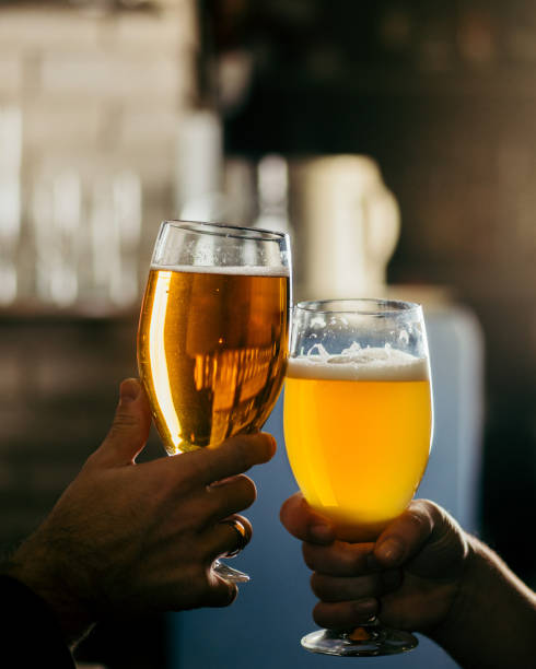 two people clink glasses with beer at the bar stock photo