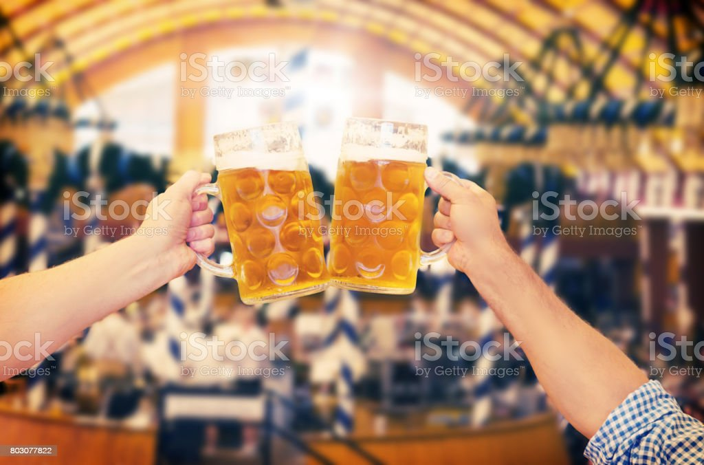Two people clinking beer glasses at the Oktoberfest stock photo