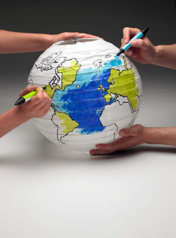Two People Coloring In A Globe Lamp Stock Photo - Download Image Now