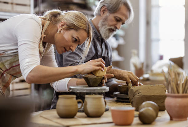 Two People Creating Pottery Two People Creating Pottery hobbies stock pictures, royalty-free photos & images
