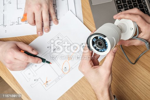 istock Two people discussing CCTV project. Video security equipment and blueprint on a table 1157139112