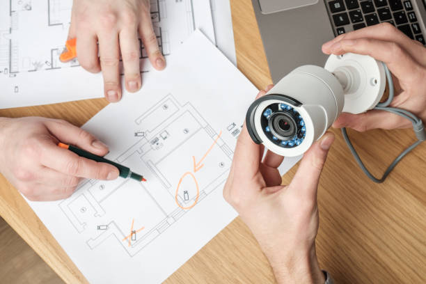 Two people discussing CCTV project. Video security equipment and blueprint on a table Two people discussing CCTV project. Video security equipment and blueprint on a table security stock pictures, royalty-free photos & images