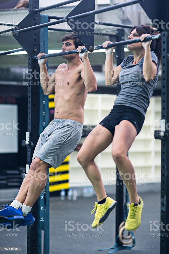 Two people doing pullups at the gym.
